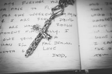 A necklace that was Mitch's late father, and also a page from his dad's journal.